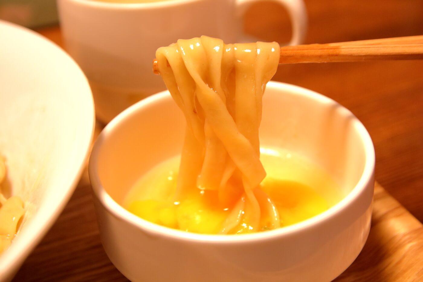 高知市一宮のラーメン店 和へる(あえる) 油そばの平打ち麺を生卵に絡めて食べる